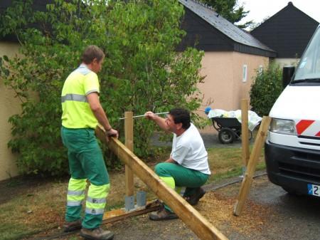 Les employés communaux installent une poutre